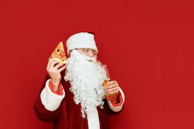 Портрет мужчины в костюме санта-клауса, держащего бутылку пива и кусок пиццы
