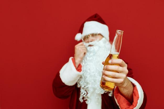 Портрет мужчины в костюме санта-клауса, держащего бутылку пива