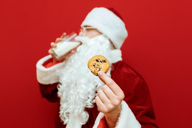 チョコレートクッキーと牛乳とプレートのガラスを保持しているサンタクロースに扮した肖像画の男