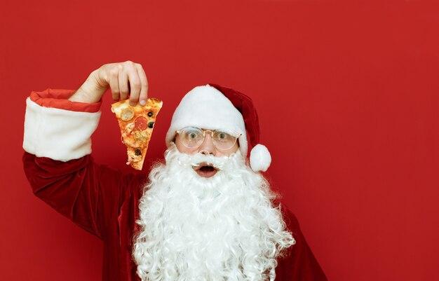 Портрет мужчины в костюме санта-клауса, держащего пиццу