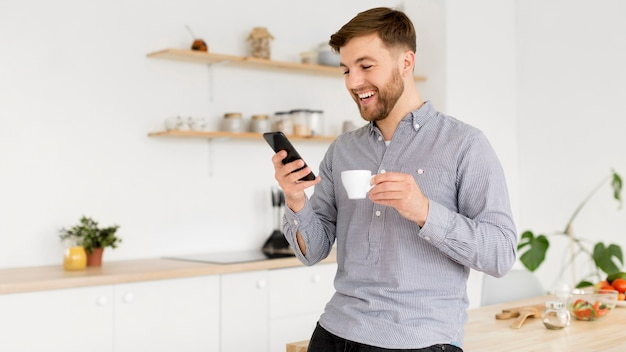 Portrait man drinking coffee while checking mobile
