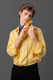 Uomo del ritratto in camicia alla moda che tiene fiore