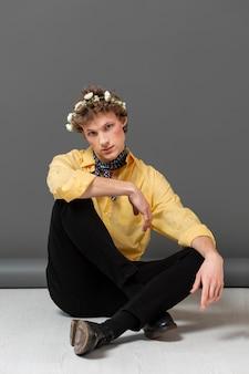 Uomo del ritratto in camicia alla moda che indossa la corona floreale