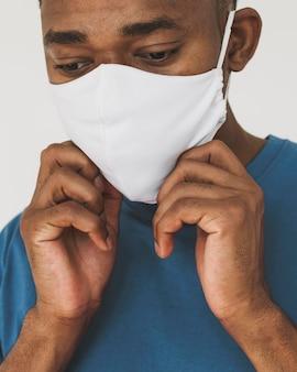 Ritratto di uomo che fissa la sua maschera per il viso