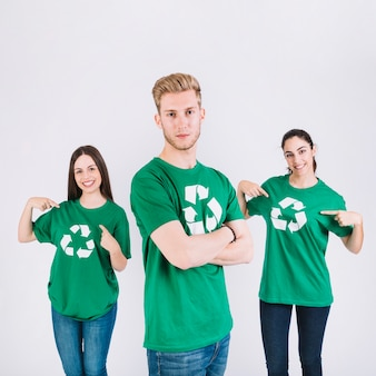Portrait of a man in front of his female friends showing recycle icon on their green t-shirt