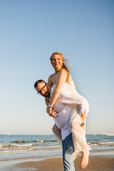 Portrait of a man giving piggyback ride to her cheerful wife on beach against blue clear sky