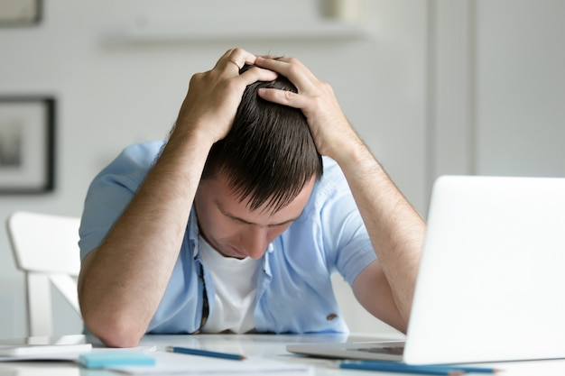 Portrait of man grabbing his head in despair near laptop