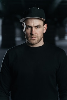 Portrait of man he is wearing a black sweatshirt and cap copy space for your advertising