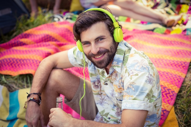 Portrait of man in headphones holding beer bottle at campsite