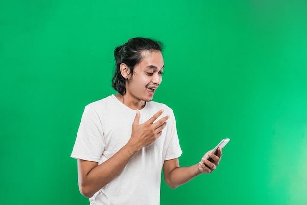 緑の背景で隔離、片手を上げている間、ショックを受けた幸福の表現と携帯電話を保持し、見て肖像画