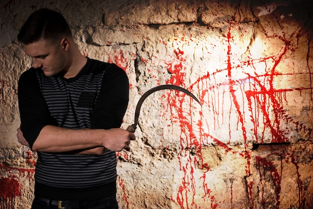 Portrait of a man holding a blade standing near blood stained wall for concept about murder and scary halloween holiday