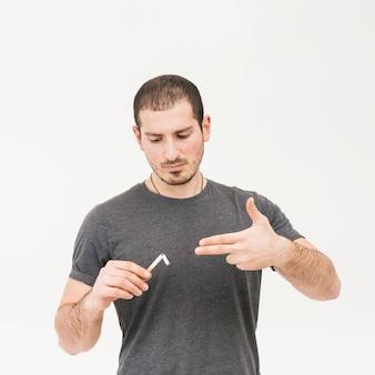 Portrait of a man holding broken cigarette making handgun gesture against white background
