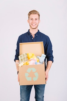Portrait of a man holding cardboard box full of garbage with recycle icon