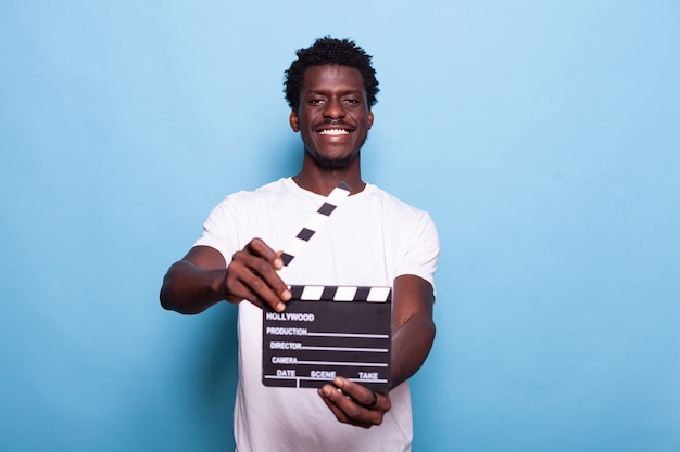 Portrait of man holding clapperboard to cut scenes