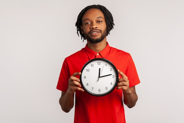 Portrait of man holding clock and smiling, happy to finish work, deadline.