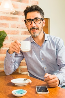 Portrait of a man holding coffee cup in hand with mobile phone on table