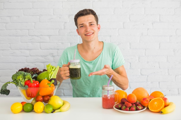 Portrait of a man holding green smoothie jar with many healthy food on table