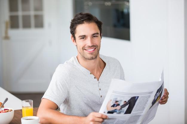 Portrait of man holding newspaper