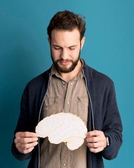 Portrait of man holding paper brain