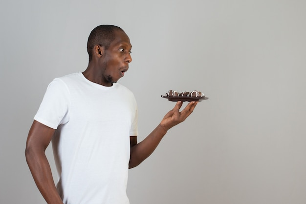 Portrait of man holding plate of sweet cookies on gray wall