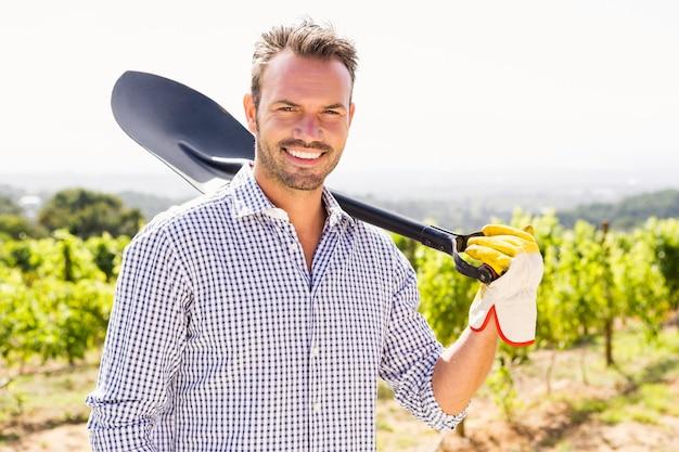 Portrait of man holding shovel at vineyard
