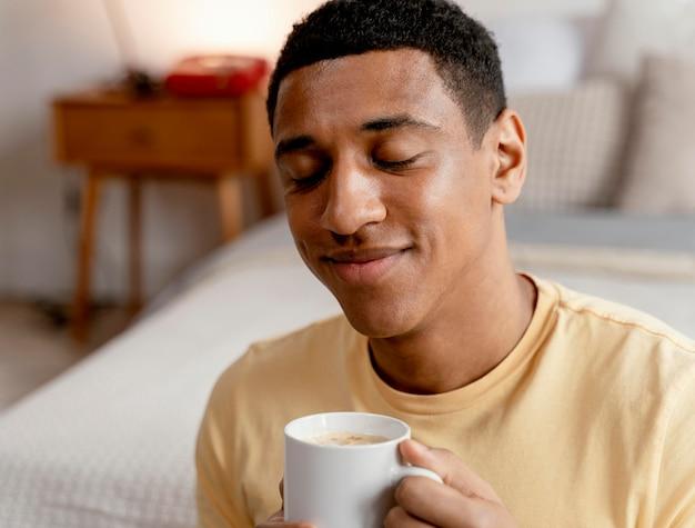 Ritratto uomo a casa a bere una tazza di caffè