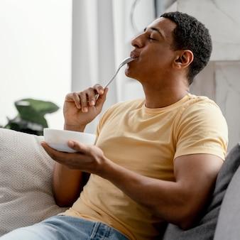 Uomo del ritratto a mangiare a casa Foto Gratuite