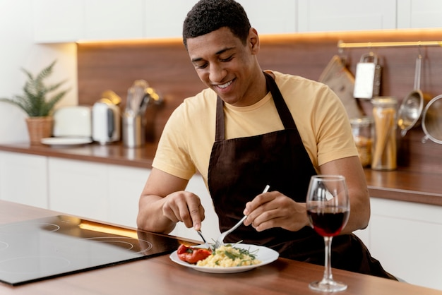 Uomo del ritratto a mangiare a casa