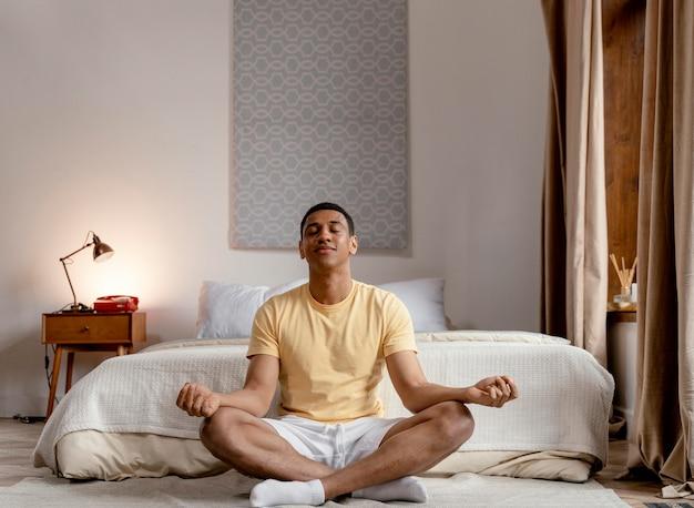 Uomo del ritratto a casa meditando