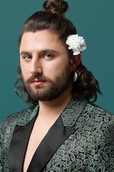 髪に花を保持しているファッショナブルな服を着た肖像画の男