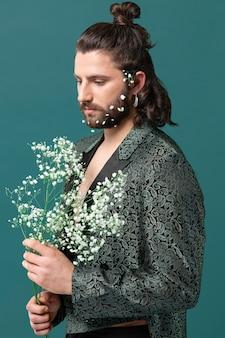 花を保持しているファッショナブルな服を着た肖像画の男
