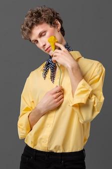 花を保持しているファッショナブルなシャツの肖像画の男