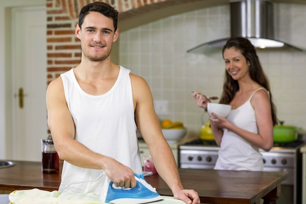 Portrait of man ironing a shirt while woman having breakfast in background