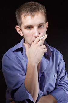 Portrait of a man is  smoking in the studio