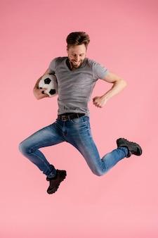 Ritratto uomo che salta tenendo palla calcio