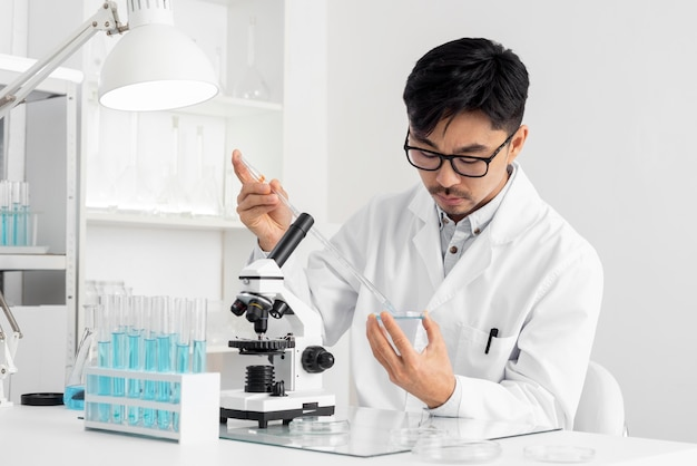 Portrait man in lab working with microscope