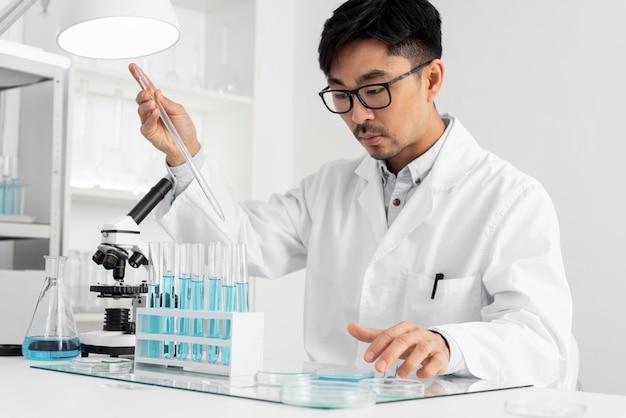 Uomo del ritratto in laboratorio che lavora con il microscopio