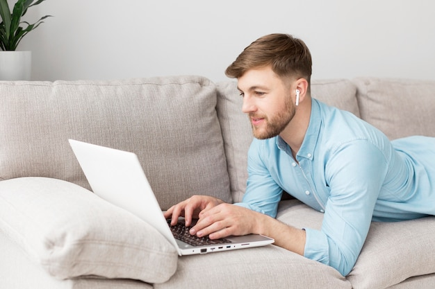 Portrait man laid on couch with laptop