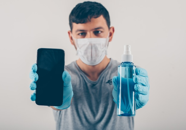 Portrait of a man at light background holding a phone and hand sanitizer in medical gloves and mask