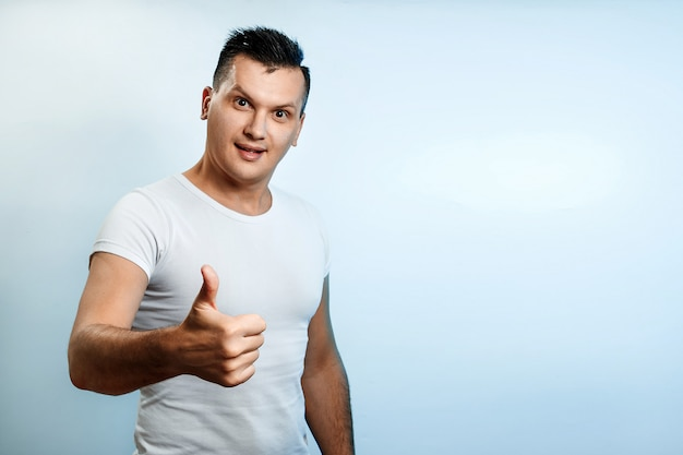 Portrait of a man on a light background, shows a thumbs up, puts a like.