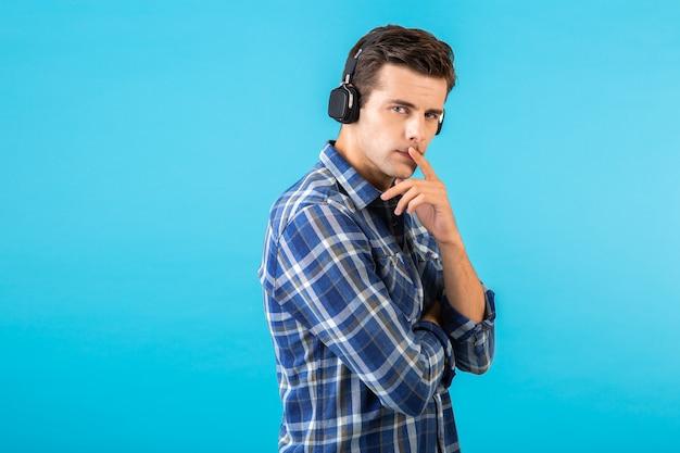 Ritratto dell'uomo che ascolta la musica sulle cuffie senza fili divertendosi sull'azzurro