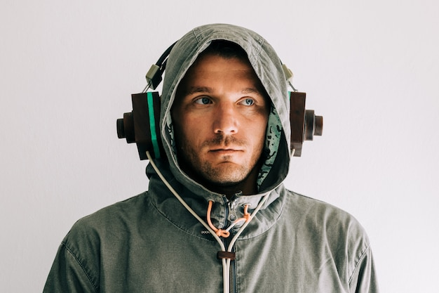 Portrait of a man listening music with wooden headphones, wearing hoodie.