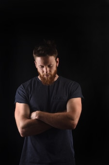 Portrait of a man look down and with arms crossed and black