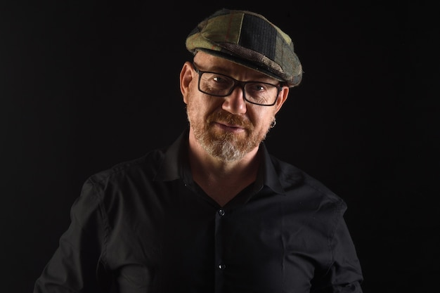 Portrait of a man in low key,front view  with cap and eyewear