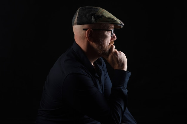 Portrait of a man in low key,looking side with  hand on chin and cap and eyewear