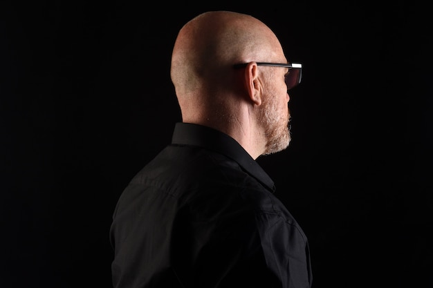 Portrait of a man in low key, rear view of head and eyewear