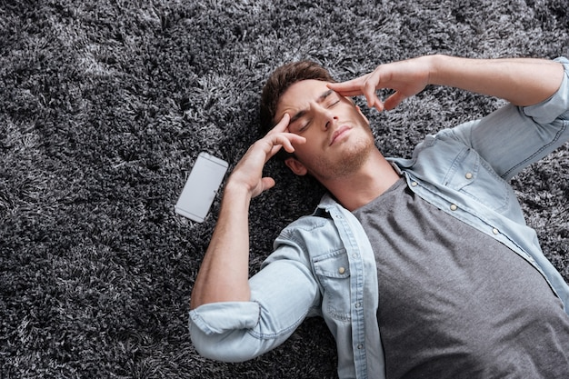 Portrait of a man lying on the floor with eyes closed and having a headache
