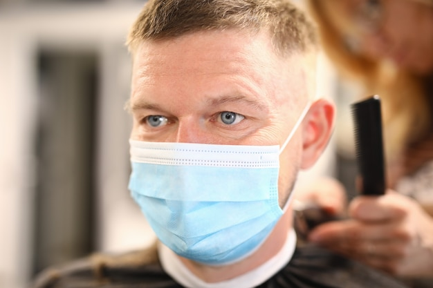 Portrait of man in medical protective mask who is being cut in barbershop.