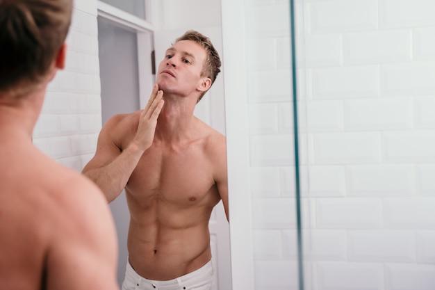 鏡の前部反射で肖像画男の筋肉体