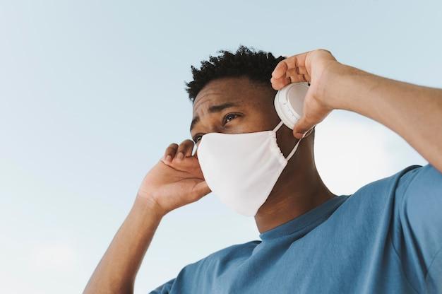 Ritratto di uomo al di fuori con le cuffie e la maschera per il viso